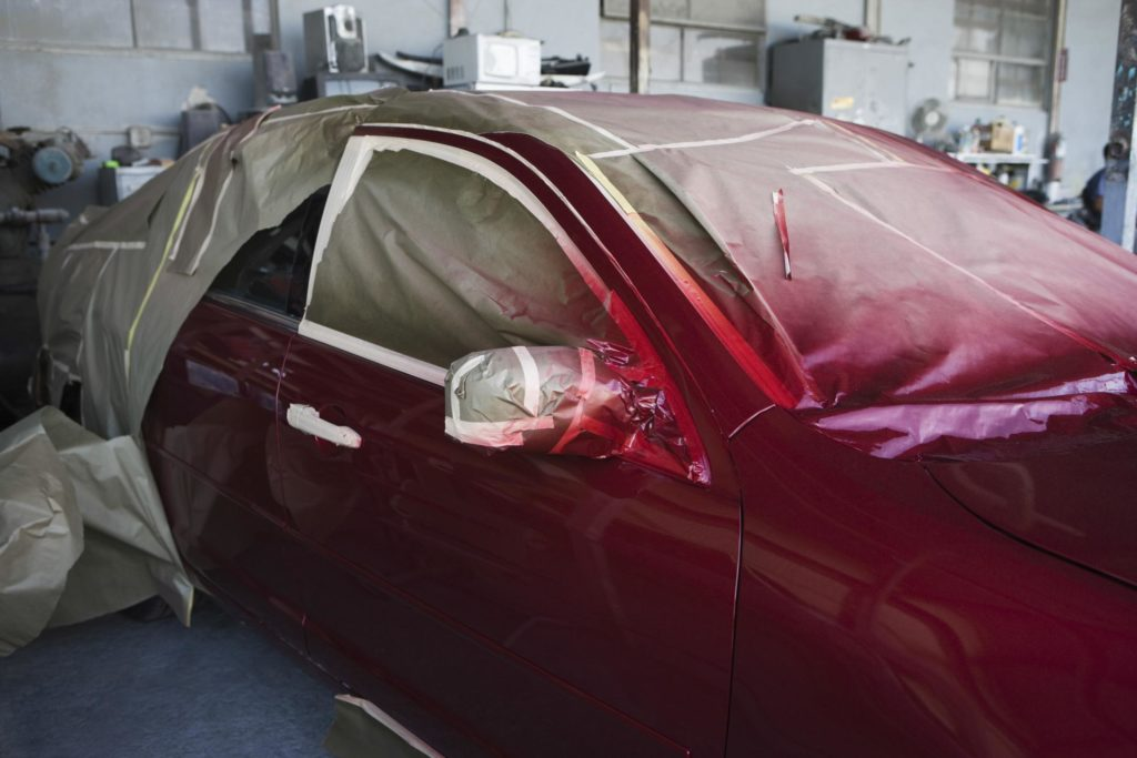 professional auto mechanic expert painting car red