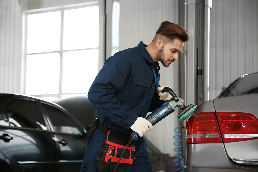 professional auto mechanic expert polishing car